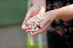 Kobiet ręki trzyma perełkowego koralika jewellery Zbliżenie żeńska ręka z perełkową biżuterią Żeńska ręka trzyma sznurek perła Zdjęcie Stock