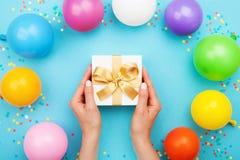 Kobiet ręki trzyma prezent lub teraźniejszości pudełko na błękita stole dekorowali kolorowych balony i confetti mieszkanie nieatu zdjęcia royalty free