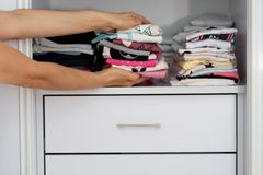 Kobiet ręki trzyma stert tkanin kolorowy bieliźniany odziewać obrazy stock