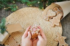 Kobiet ręki trzymają domowej roboty Bożenarodzeniowych piernikowych ciastka z cukrowym mrożeniem na pięknym drewnianym tle Choink fotografia royalty free