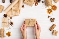 Kobiet ręki trzymają prezent rzemiosło papier Przeciw tłu wysuszona pomarańcze, cynamon, sosna konusuje, anyż na białym stole obrazy stock
