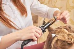 Kobiet ręki używać fryzowania żelazo zdjęcia royalty free