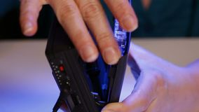 Kobiet ręki umieszczają ścisłą muzyczną kasetę w retro odtwarzaczu przenośnym zbiory wideo
