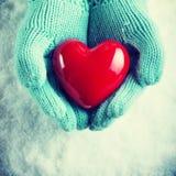 Kobiet ręki w lekka cyraneczka dziać mitynkach trzymają pięknego glansowanego czerwonego serce w śniegu Miłość i St walentynki po Obraz Royalty Free