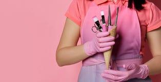 Kobiet ręki w różowym medycyn rękawiczek chwyta gofrze konusują z muśnięciem, nożyce, gwóźdź kartoteka z ściernym zdjęcie royalty free