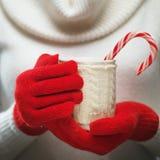 Kobiet ręki w woolen czerwonych rękawiczkach trzyma wygodnego kubek z gorącym kakao, herbata, kawa lub cukierek trzcina, Zdjęcie Stock
