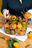 Kobiet ręki z żelaznym koszem z świeżą clementine kopii przestrzenią zdjęcia royalty free
