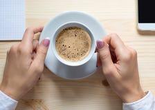 Kobiet ręki z białą filiżanką americano kawa i czerepem telefon komórkowy dalej wjjden stół, zakończenie w górę, odgórny widok obrazy royalty free