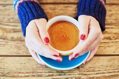 Kobiet ręki z czerwonym manicure'em i filiżanką świeża gorąca kawa na drewnianym stole Obrazy Stock