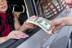 Kobiet ręki z dolarową wiązką i samochodem zdjęcie stock