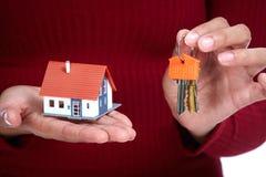 Kobiet ręki z małym domem i kluczem Fotografia Stock