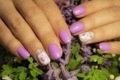 Kobiet ręki z manicure'em na fiołku kwitną tło zbliżenie zdjęcia royalty free