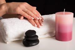 Kobiet ręki z Ombre manicure'u gwoździami na białym ręczniku i aromatycznej świeczce zdjęcie stock