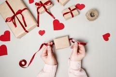 Kobiet ręki z prezentów pudełkami, czerwonym faborkiem i sercami na bielu plecy, Obrazy Royalty Free
