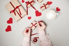Kobiet ręki z prezentów pudełkami, czerwonym faborkiem i sercami na bielu plecy, Zdjęcia Stock