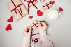 Kobiet ręki z prezentów pudełkami, czerwonym faborkiem i sercami na bielu plecy, Zdjęcie Royalty Free