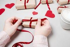 Kobiet ręki z prezentów pudełkami, czerwonym faborkiem i sercami na bielu plecy, Fotografia Stock