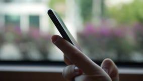 Kobiet ręki z telefon komórkowy jazdą w autobusie Zbliżenie strzał kobieta używa mądrze telefon w autobusie, okno z przelotnym mi zbiory