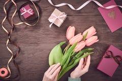 Kobiet ręki z tulipanami i prezenta pudełkiem na drewnie Obraz Royalty Free