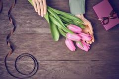 Kobiet ręki z tulipanami i prezenta pudełkiem na drewnie Zdjęcia Royalty Free