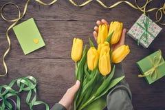 Kobiet ręki z tulipanami i prezenta pudełkiem na drewnie Obrazy Royalty Free