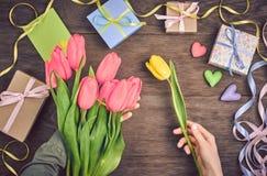 Kobiet ręki z tulipanami i prezenta pudełkiem na drewnie Fotografia Stock