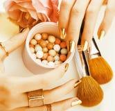 Kobiet ręki z złotym manicure'em i wiele pierścionkami trzyma muśnięcia, makeup artysty materiał elegancki, czyste zakończenie me Fotografia Royalty Free
