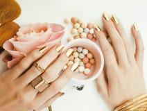 Kobiet ręki z złotym manicure'em i wiele pierścionkami trzyma muśnięcia, makeup artysty materiał elegancki, czysty zakończenie up Obrazy Stock