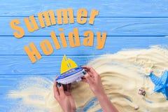 Kobiet ręki z zabawkarską łodzią wakacje letni inskrypcją na błękicie zdjęcie royalty free