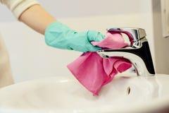 Kobiet ręki z zielonymi gumowymi ochronnymi rękawiczkami czyści klepnięcie Fotografia Stock
