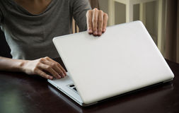Kobiet ręki zamykają laptop w dnia czasu ostrości ręce w domu Zdjęcie Royalty Free