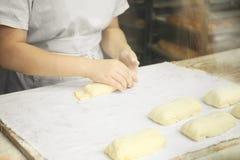 Kobiet r?ki przygotowywa kulebiaki od surowego ciasta zdjęcia stock