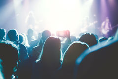 Kobiet ręki trzyma ich smartphone i fotografuje rockowego przeciw Fotografia Stock