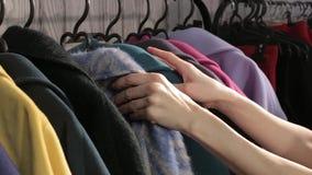 Kobiet ręki wybiera kolorowych ubrania na wieszakach zdjęcie wideo