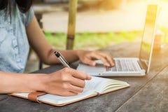 Kobiet ręki z pióra writing notatnikiem Obrazy Royalty Free