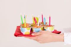 Kobiet ręki trzyma jaskrawą tacę z muffins i urodzinowymi świeczkami Świętowanie urodziny Obrazy Royalty Free