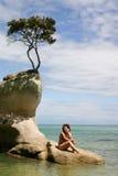 Kobiet siedzenia na rockowym Abel Tasman parku, Nowa Zelandia Obrazy Stock