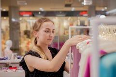 Kobiet spojrzenia przy dalej odziewają Reklamuje, sprzedaż, mody pojęcie Kobiety pozycja w sklepie, przyglądający wieszaki z odzi Obraz Royalty Free