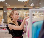 Kobiet spojrzenia przy dalej odziewają Reklamuje, sprzedaż, mody pojęcie Kobiety pozycja w sklepie, przyglądający wieszaki z odzi Zdjęcia Stock