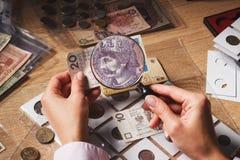 Kobiet spojrzenia przy złoty rachunkiem przez powiększać - szkło Obrazy Stock