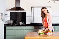 Kobiet Tnący warzywa Przy Kuchennym kontuarem zdjęcia stock