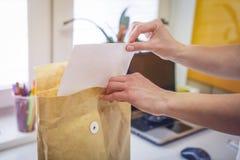 Kobiet wszywek dokument w brown kopertę na tle biurowy zakończenie Kobiet ręki i brown koperta Obrazy Stock