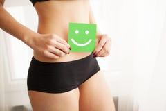 Kobiet zdrowie Zbliżenie Zdrowa kobieta Z Pięknym napadu schudnięcia ciałem Trzyma zieloną kartę Z Szczęśliwym W Czarnych majtasa zdjęcie stock