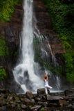 Kobieta ćwiczy joga przy Gitgit siklawą na Bali w Indonesia Zdjęcie Stock