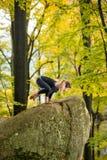 Kobieta ćwiczy joga w jesień lesie na dużym kamieniu obrazy royalty free