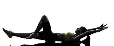 Kobieta ćwiczy sprawności fizycznej rozciągania lying on the beach na plecy   sylwetka Obraz Stock