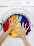 Kobieta ładuje kolorową pralnię w pralce Obraz Stock
