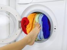 Kobieta ładuje kolorową pralnię w pralce Obraz Royalty Free