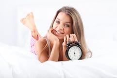 Kobieta łgarski puszek na łóżkowym ang mienia budziku Obraz Stock