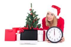 Kobieta łgarski puszek z zegarem, notatnikiem, choinką i prezentami, Fotografia Royalty Free